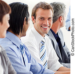 Delighted businessman looking at the camera in a meeting...