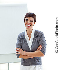 Confident businesswoman with folded arms in front of a board...