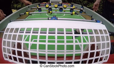 Friends playing table soccer outdoor camera mounted at the...