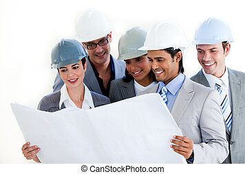Multi-ethnic architects studying a blueprint against a white...
