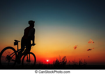 Silhouette of a biker and bicycle on sky background. -...