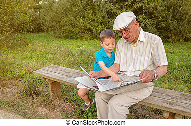 Senior man and child reading a newspaper outdoors - Senior...