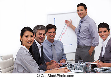 Cheerful male executive reporting sales figures in a meeting