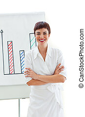 Smiling businesswoman with folded arms in front of a board...