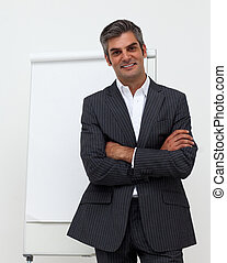 Businessman with folded arms in front of a board - Mature...