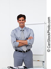Charming businessman with folded arms in front of a board at...