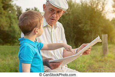 Senior man and child reading a newspaper outdoors - Closeup...