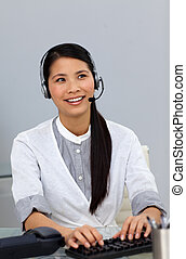 Delighted businesswoman with headset on working at a computer