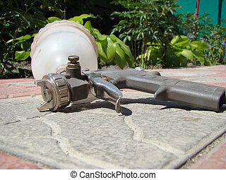 spray - gun lies on the tile,is used for spraying paint with...