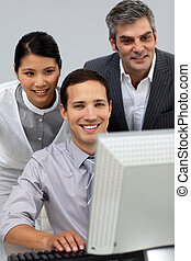 Diverse business partners working together at a computer