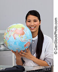 Assertive asian businesswoman holding a globe