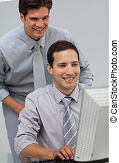 Self-assured businessman helping his colleague at a computer