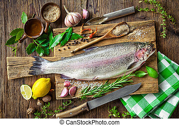 Fresh trout with spices and seasoning on cutting board