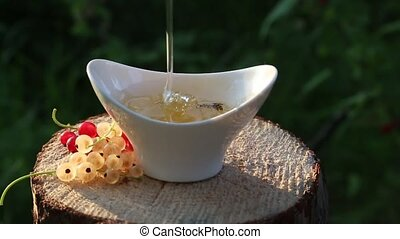 Quality honey pouring a continuous stream and creates the...
