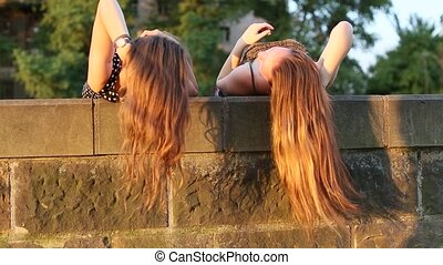 Two young girls lying and talking