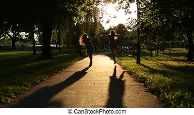 Silhouettes of two girls walking