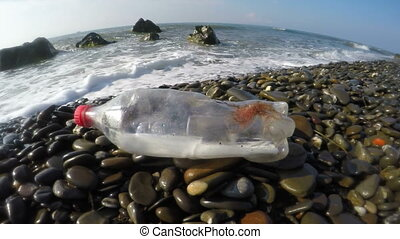 Plastic bottle brought to wild shore by sea waves