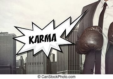 Karma text with businessman wearing boxing gloves on...
