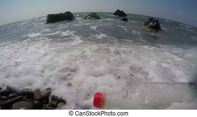 Plastic bottle with message brought to shore by sea waves...