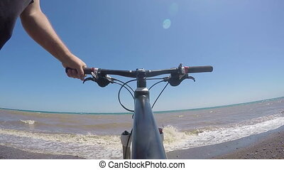 Traveler with bicycle standing on the beach looking at the seascape POV