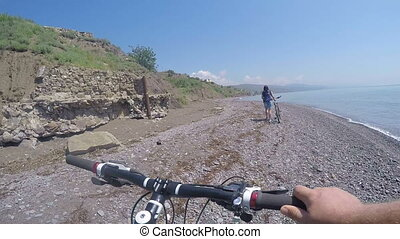 First-person POV Cyclists travelers pushing bikes along the...