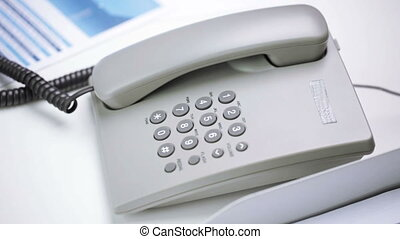 hands dialing number on desk set phone at office - business,...