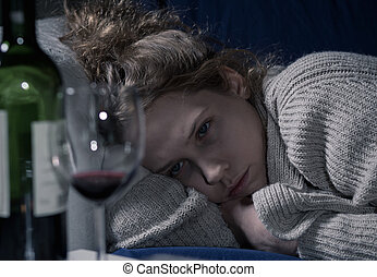 Drunk woman on couch - Young drunk sad woman lying on couch