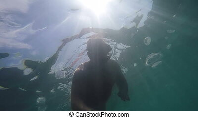 Underwater shot of man snorkeling in sea water swimming with...