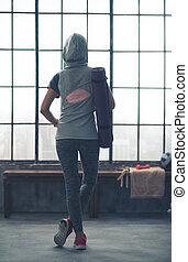 Woman standing relaxing in gym seen from behind wearing...