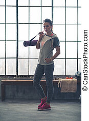 Serious woman in workout gear holding yoga mat in loft gym -...