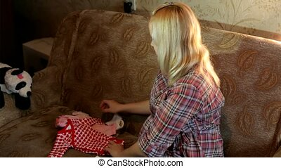 Kid Stuff - Expectant mother is sitting on the couch and...