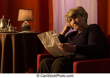 Receiving bad news - Elderly woman after reading a letter...