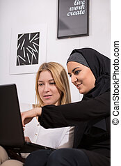 Looking at photos - Muslim and caucasian girls looking at...