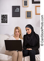Christian and muslim girls watching film on laptop