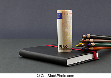 Multiple color pencils with euro currency and black journal...