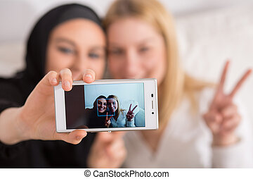 Selfie with friend - Young muslim woman doing selfie with...