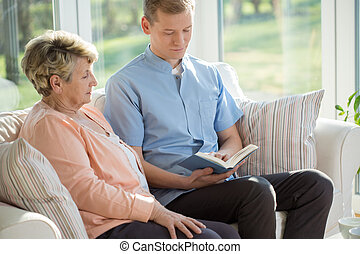 Male nurse reading book to old woman