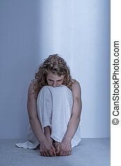 Curled up scared rape victim in empty room