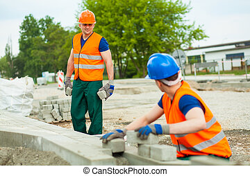 Young pavers working at a construction site