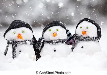 Three cute snowmen in a snow storm