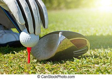 Golf Ball - Hand placing a golf ball on a tee, next to a...
