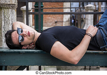Attractive young man laying down on wood bench in European...
