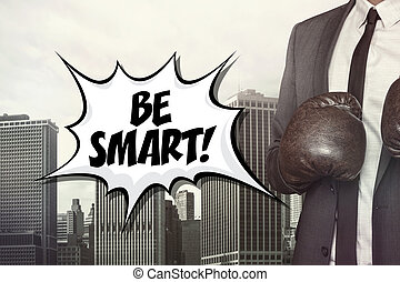 Be smart text with businessman wearing boxing gloves on...