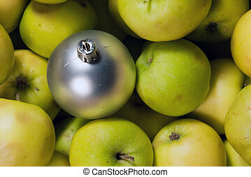 Fruitful new year. Gray xmas ball on a green apples