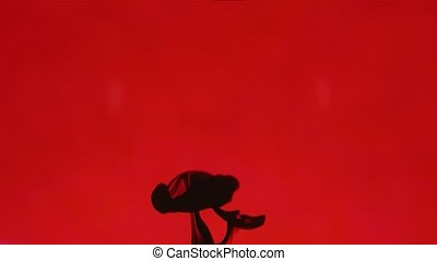 Beautiful Abstract - Black ink is poured into water on a red...