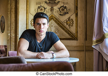 Relaxed Young Man Sitting Comfortably at Table - Portrait of...