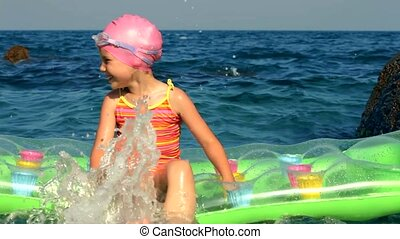 Cheerful Girl On A Mattress In The Sea - The little girl is...
