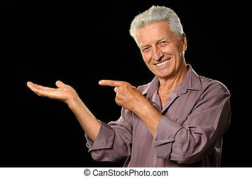 Mature man pointing with his finger on black background