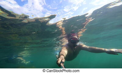 Couple with snorkeling gear exploring underwater world in sea water