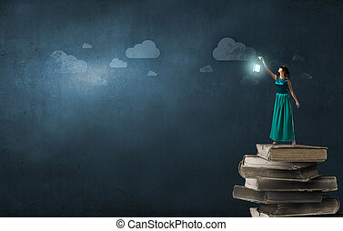 Lost in darkness - Young woman in green dress with lantern...